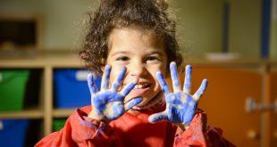 Happy little girl painting with hands in kindergarten
