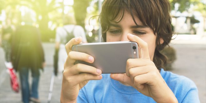 boy playing with smartphone in street