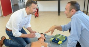 Men training to use defibrillator