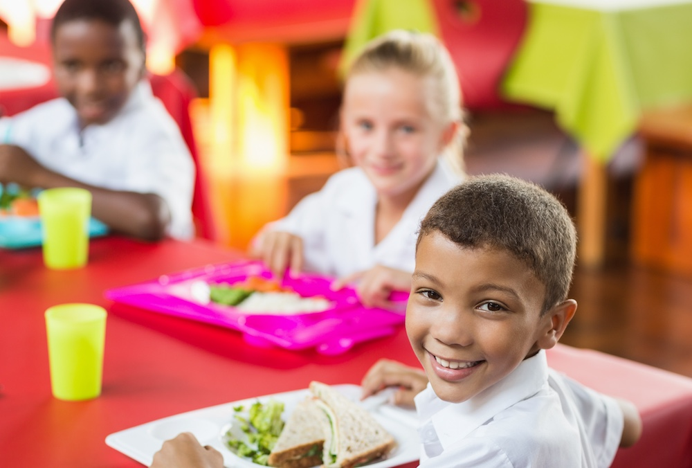 Children having healthy lunch during break time in school