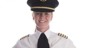 Female pilot in uniform and wearing her hat