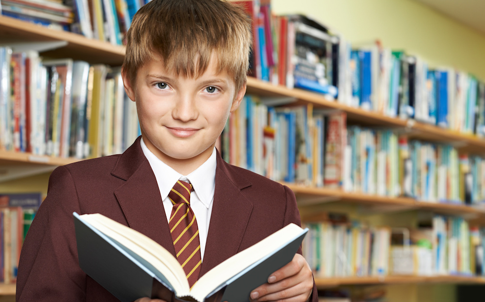 Boy Wearing School Uniform Reading Book In Library