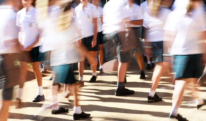 Wide view of large amount of male and female school students wearing neat uniforms moving between classes in a high school yard environment. deliberate heavy motion blur to convey sense of movement